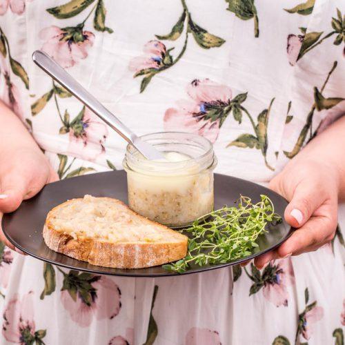 kobieta trzyma talerz z kromką chleba, smalcem z gęsi oraz z ziołami, nóż w słoiku